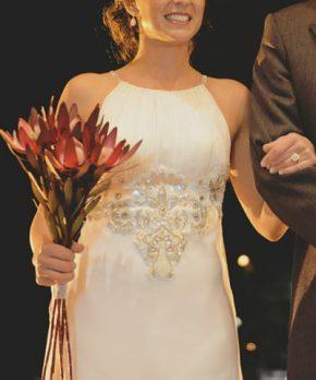 Vestido de novia con escote halter y bordados en tonos mate, hueso y perla