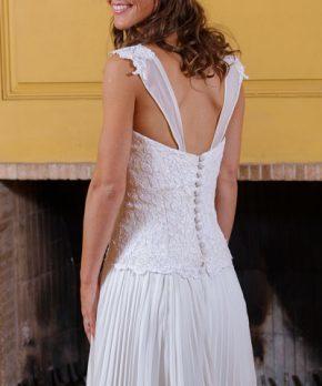 Novia con vestido de gasa plisada y encaje, espalda reducida