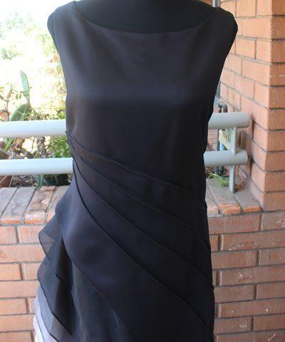 Vestido de madrina cerrado color negro con plisado y vuelos