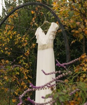 Vestido de novia en la naturaleza hecho en gasa con aplicaciones doradas en la cintura