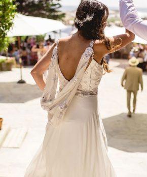 Espalda de vestido de novia rebajada con pedreria y velo