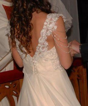 Novia con vestido de espalda rebajada y mangas de encaje