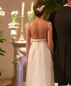 Novia con vestido de espalda rebajada y aplicaciones doradas de pedreria